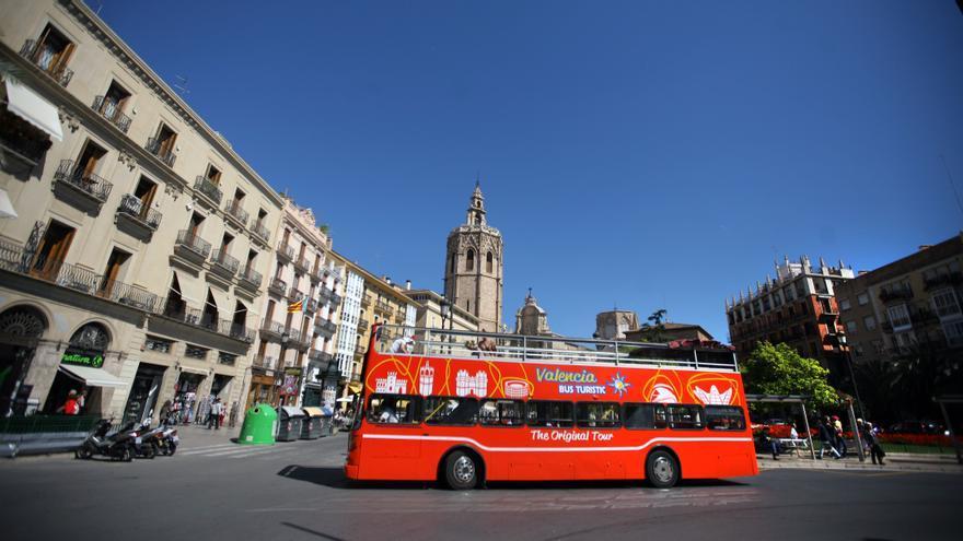 El Bus Turístic en la Plaza de la Virgen de Valencia con el Micalet al fondo