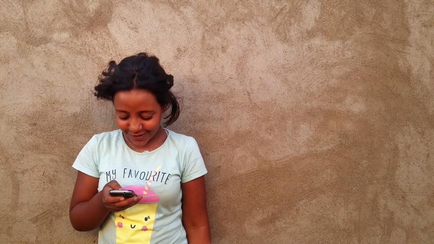 Asma, refugiada saharaui, ve un vídeo de YouTube en el pasillo exterior de la casa de su familia.   G. S.