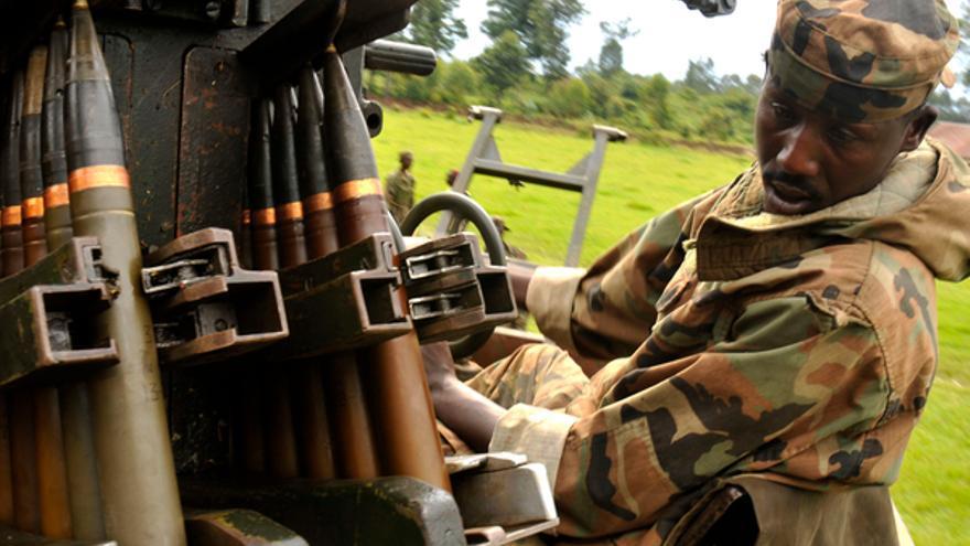 Un combatiente del Congreso Nacional para la Defensa del Pueblo, grupo rebelde, observa armas capturadas durante combates con el ejército congoleño en Rumangabo. 17 de octubre 2008. © REUTERS/ James Akena