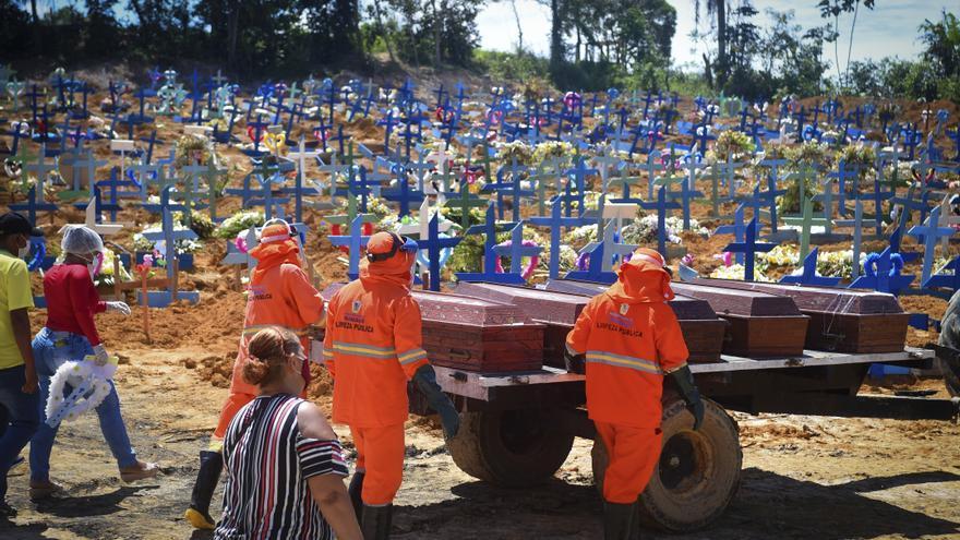 Trabajadores del cementerio y parientes de los muertos por coronavirus conducen los ataúdes a una fosa común en Manaos, Brasil, este 29 de abril