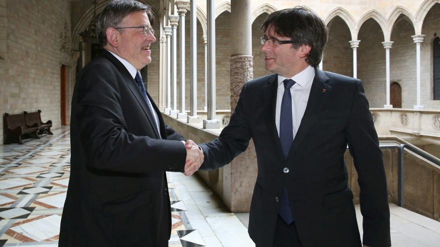Los presidente valenciano y catalán, Ximo Puig y Carles Puigdemont, se saludan