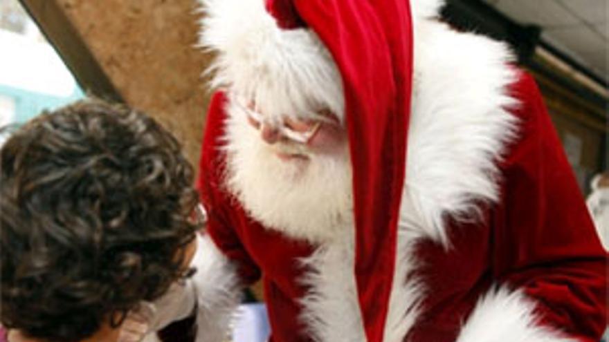 Papá Noel entrega un regalo a una niña. (ACFI PRESS)