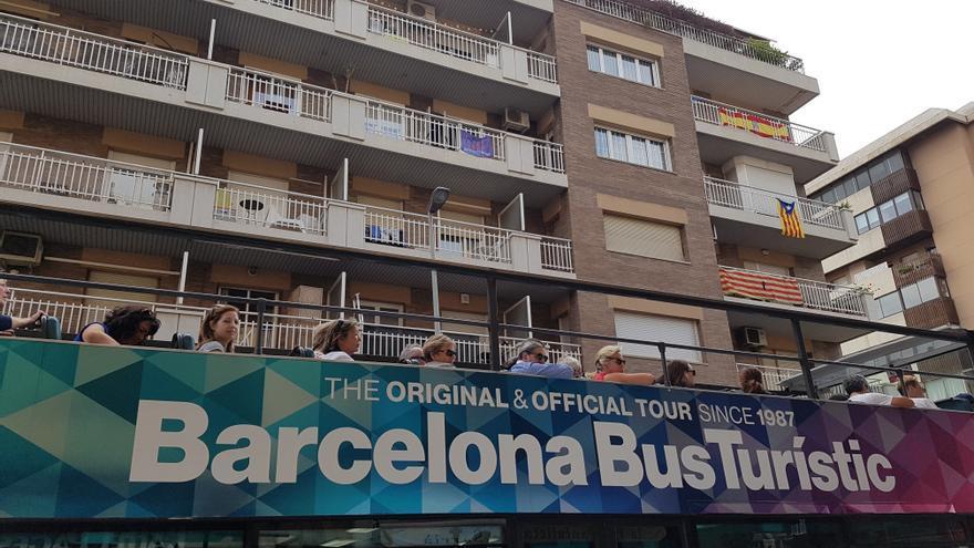 El autobús turístico de Barcelona pasa ante un edificio del barrio de Sarriá con banderas esteladas y constitucionales.