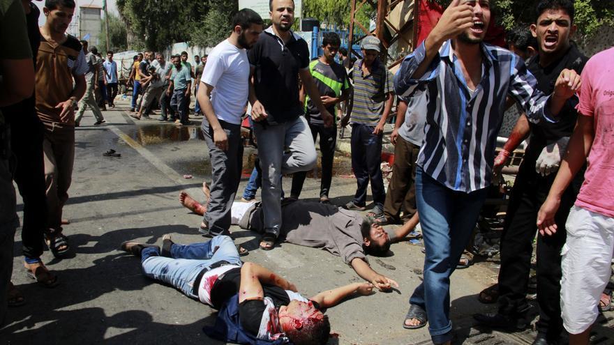 Palestinos muertos y heridos en los alrededores de la escuela de la ONU bombardeada por Israel este domingo, rodeados de varios palestinos / Hatem Ali \ AP Photo