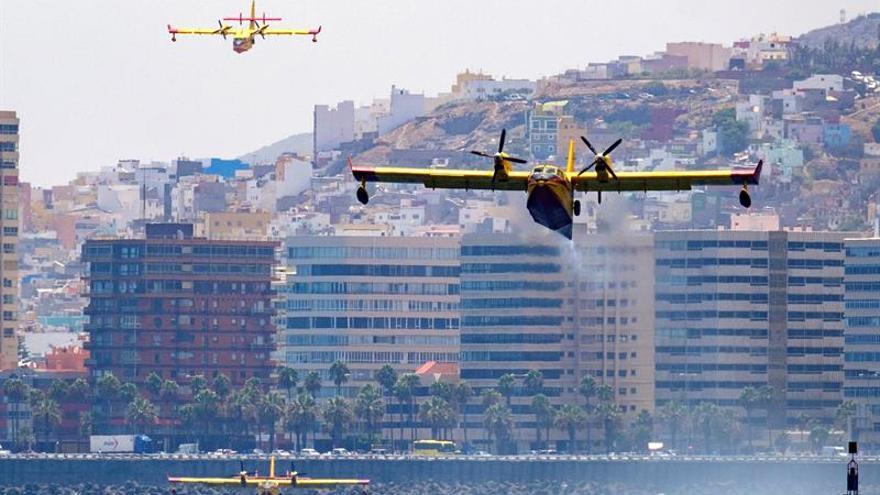 Tres de los cuatro hidroaviones que trabajan en las labores de extinción del incendio de Gran Canaria, cargan agua en la bahía de la capital grancanaria. EFE/Ángel Medina G.