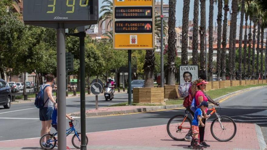 Varios niños acompañados por sus padres pasan junto a un termómetro que marca 39º centígrados en Murcia.