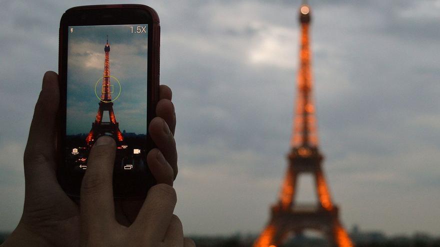 Una persona fotografía la Torre Eiffel con su smartphone