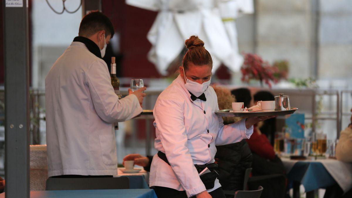 Dos camareros trabajan en la terraza de un bar en el centro de Madrid (España)