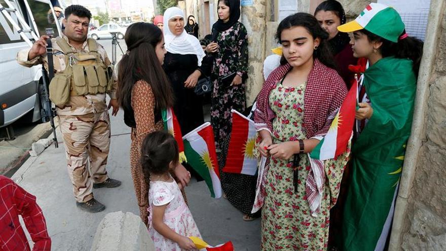 Un grupo de personas espera para votar en el referéndum del domingo en un colegio electoral en Erbil.