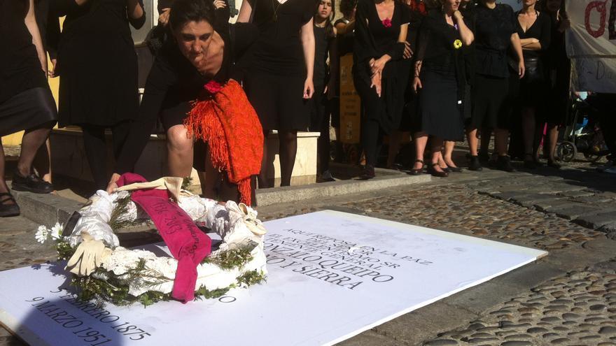 Una mujer deja una corona de flores con el lema 'Las mujeres no olvidamos. 1936-2013'.