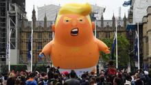 Decenas de manifestantes rodean un globo gigante que caricaturiza al presidente de Estados Unidos, Donald Trump, durante una protesta contra la visita del mandatario, este martes en Londres (Reino Unido).