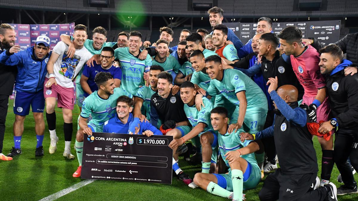 Los jugadores de Godoy Cruz muestran el cheque que obtuvieron por eliminar a Racing.