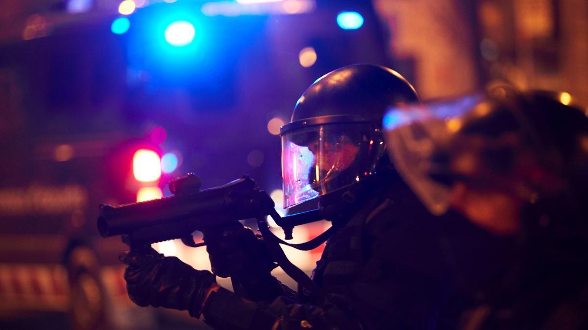 Un agente de los Mossos porta una escopeta de foam en las protestas por el encarcelamiento del rapero Pablo Hasel