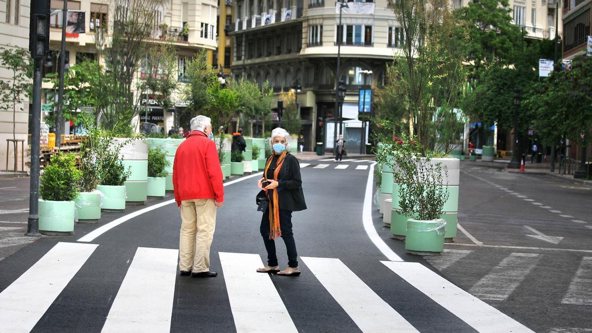 Dos viandantes observan los cambios en la plaza del Ayuntamiento de València.