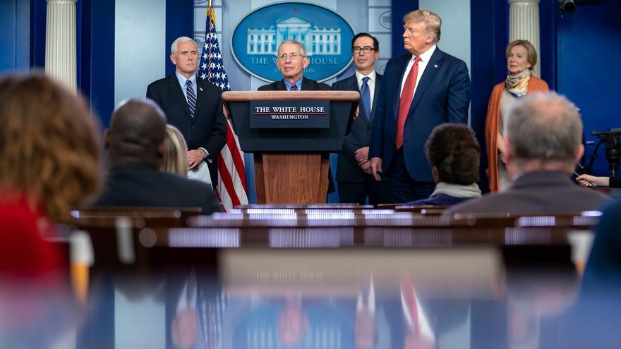 Fauci en una rueda de prensa en la Casa Blanca contemplado o vigilado por Trump.