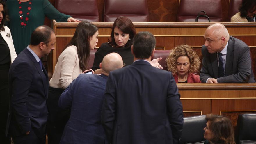La portavoz de Unidas Podemos, Irene Montero, habla con la socialista Adriana Lastra en presencia de Pedro Sánchez y diputados del PSOE
