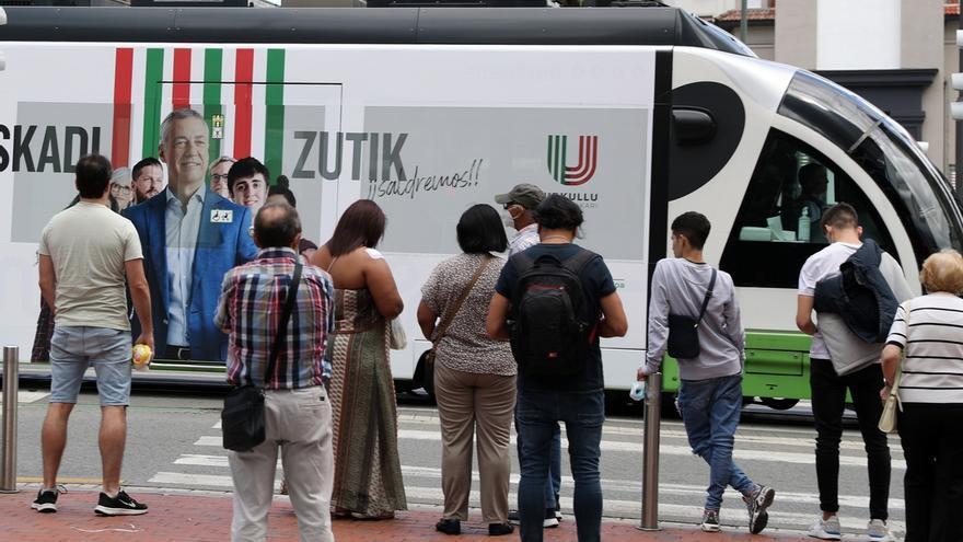 Ciudadanos observan este viernes en Bilbao, un tranvía con publicidad electoral del lehendakari y candidato a la reelección Iñigo Urkullu, de cara a las elecciones vascas del 12 de julio.