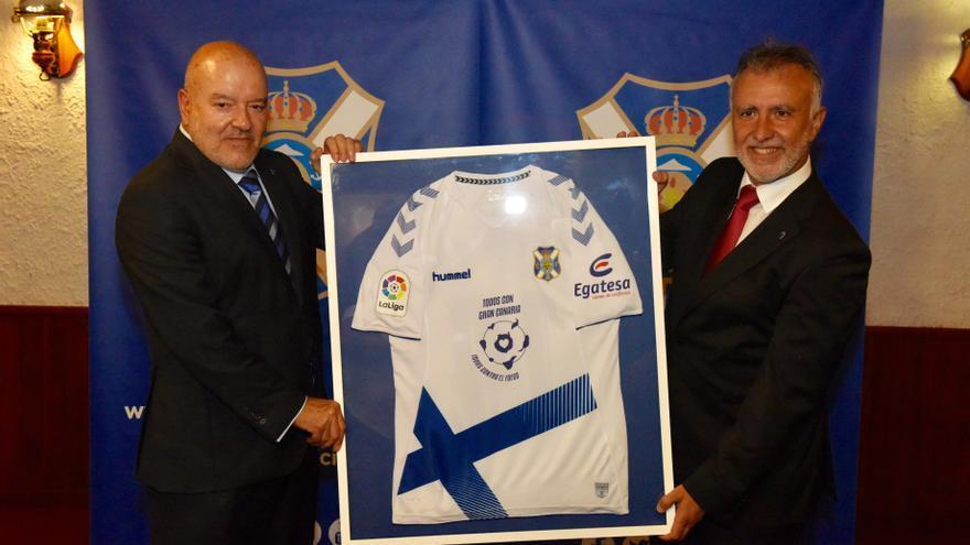 Ángel Víctor Torres recibe de manos de Miguel Concepción una camiseta del CD Tenerife con el logo creado para solidarizarse con Gran Canaria tras los incendios del pasado agosto.