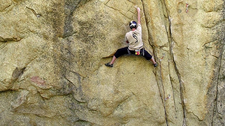 Escalador con casco y de primero con la cuerda bien colocada en caso de caída, se dispone a chapar desde una postura lo más cómoda que le permite la vía y pidiendo cuerda al asegurado, éste se la da de inmediato para que pueda chapar.