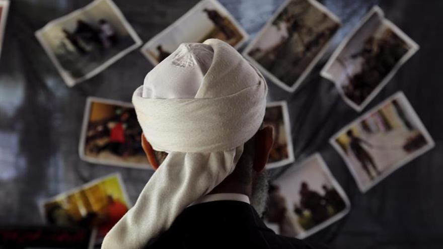 Un hombre observa fotografías de víctimas en el conflicto de Yemen, en el que se acusa a Arabia Saudí de miles de muertes.