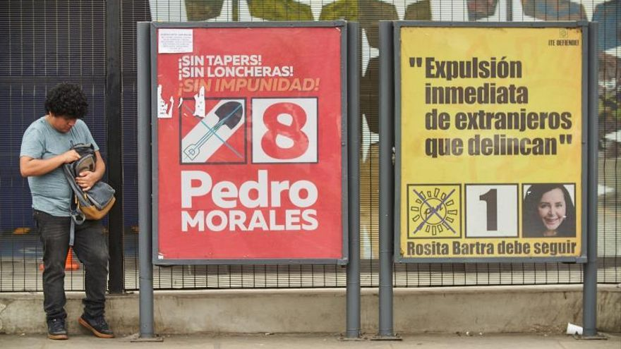 """Un ciudadano espera transporte público junto a una valla de publicidad electoral de la candidata por el partido """"Solidaridad Nacional"""" Rosa Barta este martes, en Lima (Perú)."""
