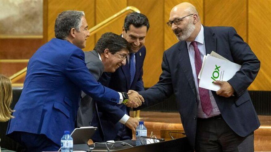 El presidente de la Junta, Juan Manuel Moreno (PP), el vicepresidente, Juan Marín (Cs) y el titular de Presidencia, Elías Bendodo, saludan al portavoz de Vox, Alejandro Hernández.