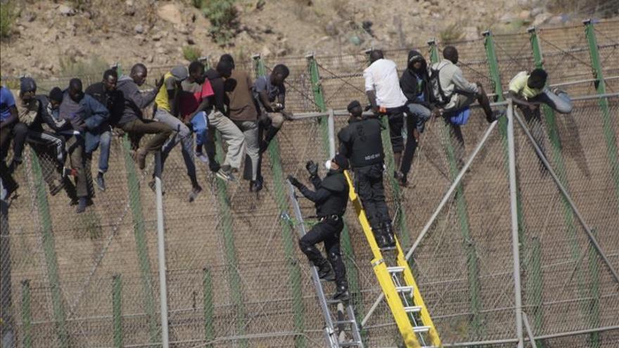 Dos de los inmigrantes encaramados a la valla de Melilla desde esta madrugada se han bajado de la verja y han sdevueltos a Marruecos de forma ilegal/ Foto: Efe