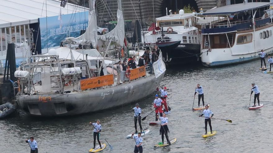 Aficionados al Stand Up Paddle remando sobre sus tablas en una travesía de varios kilómetros del río parisino.