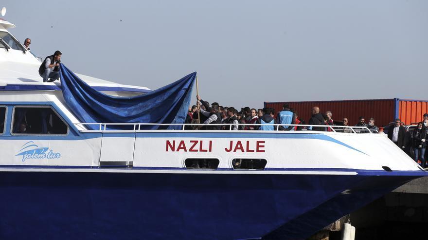 Operarios intentan tapar con una lona a los refugiados y migrantes recién llegados al puerto turco de Dikili. El primer buque de deportación de migrantes y refugiados desde la isla griega de Lesbos cuando estaba atracado en el puerto de Dikili. Al amanecer un grupo inicial fue escoltado hasta dos pequeños ferries por agentes de Frontex. El primer buque llegó a Puerto de Dikili, acompañado por la guardia costera turca. | Foto: AP - Emre Tazegul
