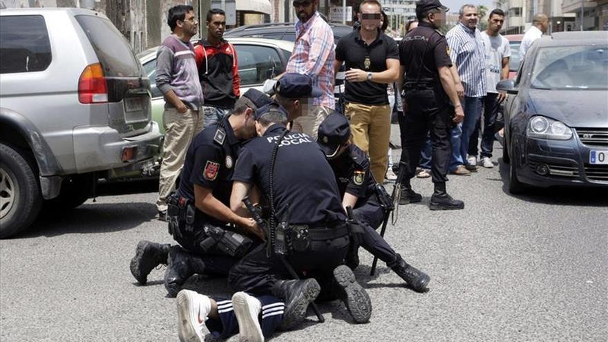 Varios policías retienen a un miembro de Coalición por Melilla ante la sede de Correos de Melilla, en la que los agentes han tenido que intervenir después de que se haya registrado un altercado entre simpatizantes de ese partido y miembros del PP, que se disponían a depositar sobres con votos en la oficina postal.