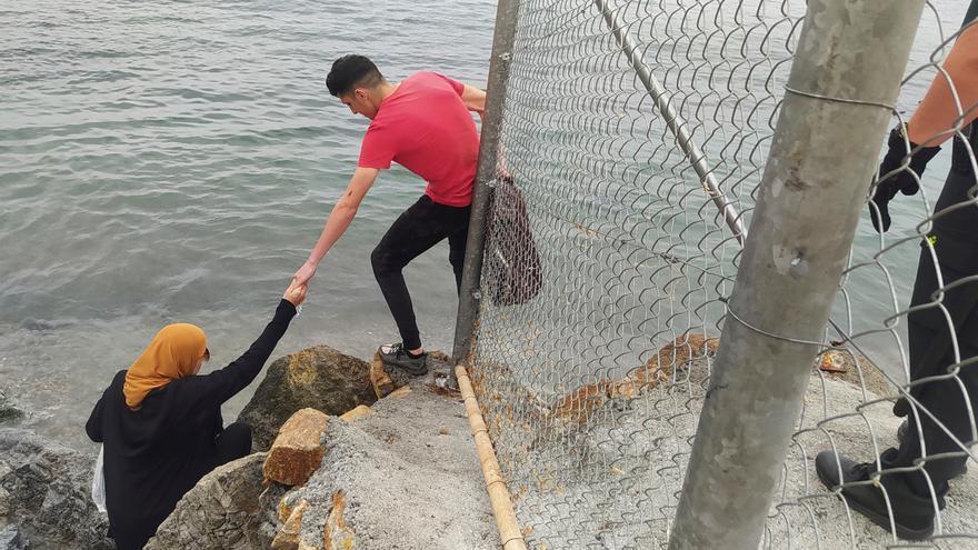 Dos inmigrantes escalan las rocas de uno de los espigones fronterizos de Ceuta. EFE/Reduan