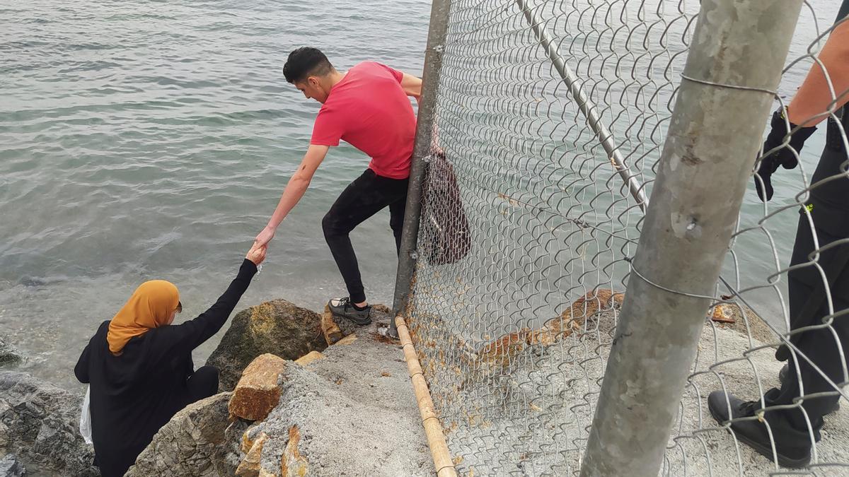 Dos inmigrantes escalan las rocas de uno de los espigones fronterizos de Ceuta.