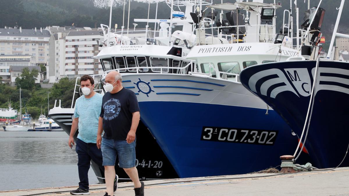 Dos hombres pasean por el puerto de Burela, en Lugo.