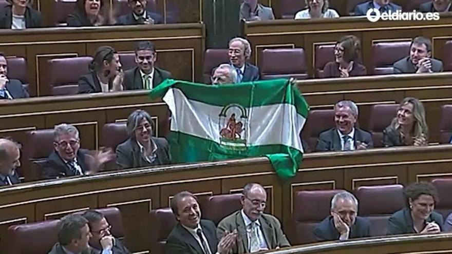 El diputado socialista Manuel Pezzi saca una bandera de Andalucía durante el discurso de Rajoy en el debate del estado de la nación de 2015.