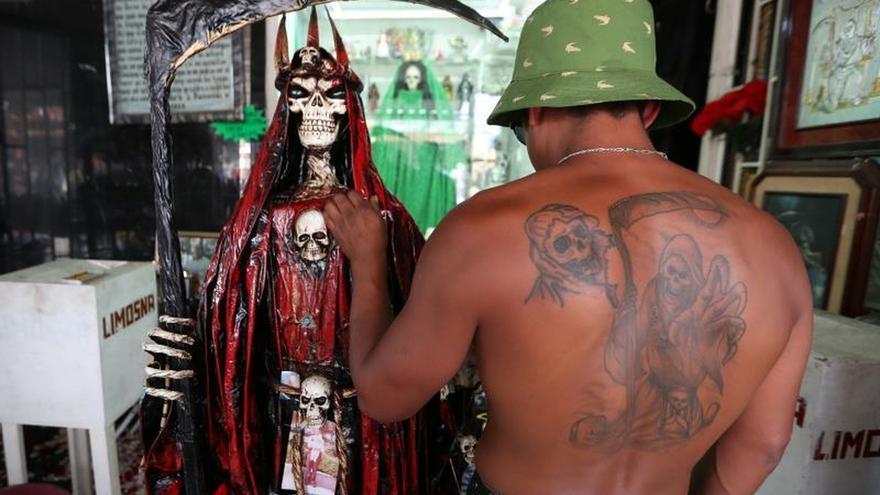 Un seguidor con un tatuaje de la Santa Muerte en su espalda acude este miércoles al altar de la figura en el popular Barrio de Tepito, en la Ciudad de México (México).