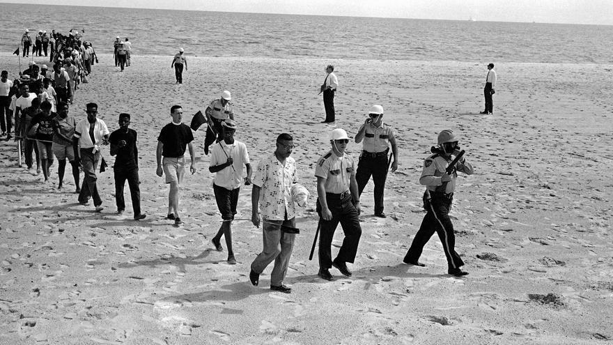 Varios manifestantes abandonan la playa de Biloxi guiados por la Policía, tras un intento fallido de acabar con la segregación racial en la costa.