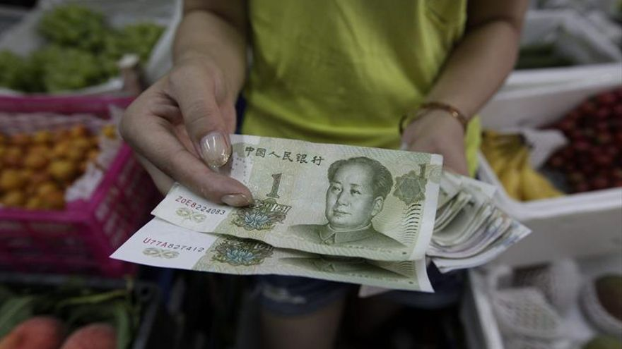 Una vendedora muestra billetes de yuan en Pekín (China).