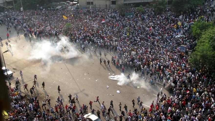 Miembros de la hermandad musulmana y partidarios del expresidente Morsi son dispersados con gas lacrimógeno durante los enfrentamientos con la policía antidisturbios en el centro de El Cairo, el 6 de octubre de 2013. © AFP PHOTO / AHMED GAMEL