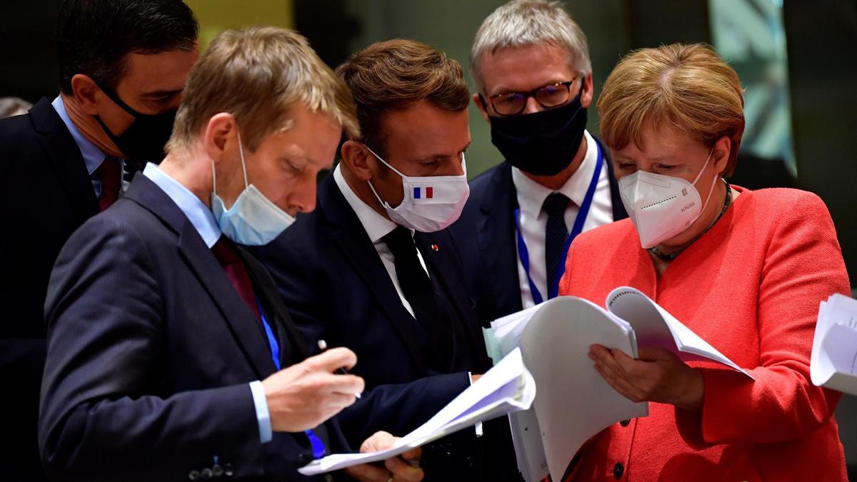 La canciller alemana Angela Merkel (d) conversa con el presidente francés Emmanuel Macron (c) en el cuarto día de la cumbre de líderes del Consejo Europeo Extraordinario, la primera reunión cara a cara entre estadistas de la UE celebrada desde la irrupción de la pandemia, en Bruselas, Bélgica.