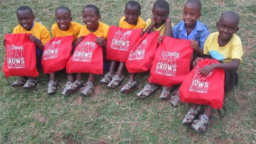 Niños ruandeses con los zapatos que crecen
