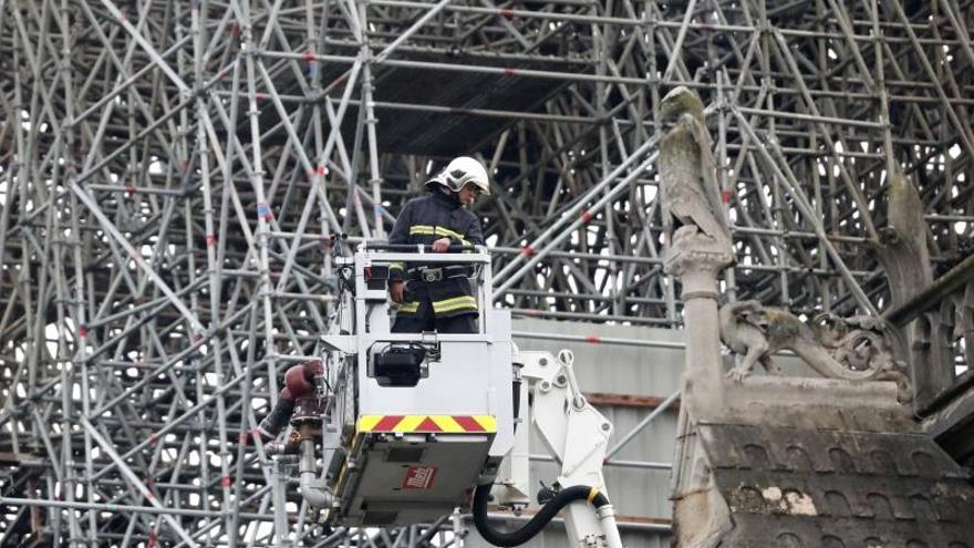 Un bombero trabaja en un elevador junto al andamiaje que cubre parte de la catedral de Notre Dame, este martes en París (Francia)