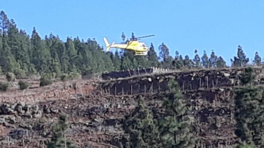 Un helicóptero opera en la zona afectada por el fuego en el monte de Granadilla