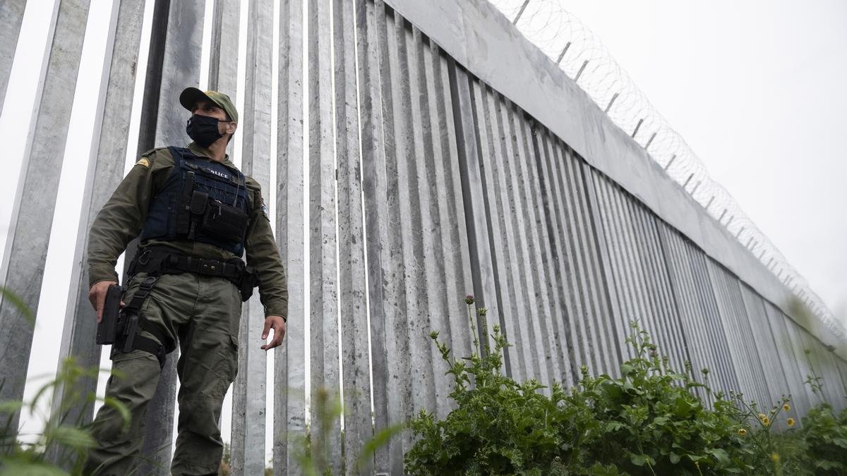 Un policía patrulla junto a un muro de acero en el río Evros, en la frontera entre Grecia y Turquía.