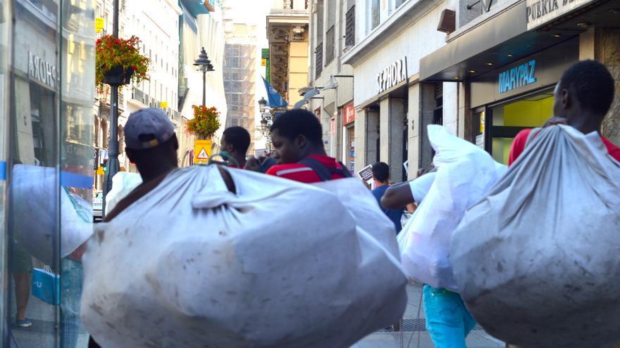 Ante la llegada de la Policía, varios manteros recogen su mercancía y se marchan de donde estaban vendiendo   FOTO: P.R.