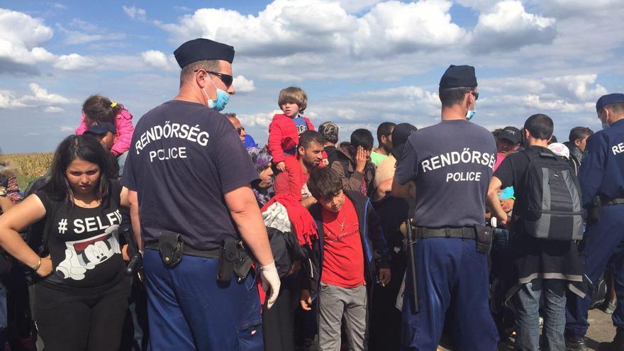 La policía húngara obliga a los refugiados a aguardar durante horas de pie, bajo el sol, en una fila / Olga Rodríguez