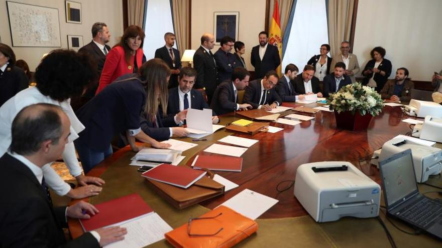 Los presos independentistas firman sus credenciales como diputados.