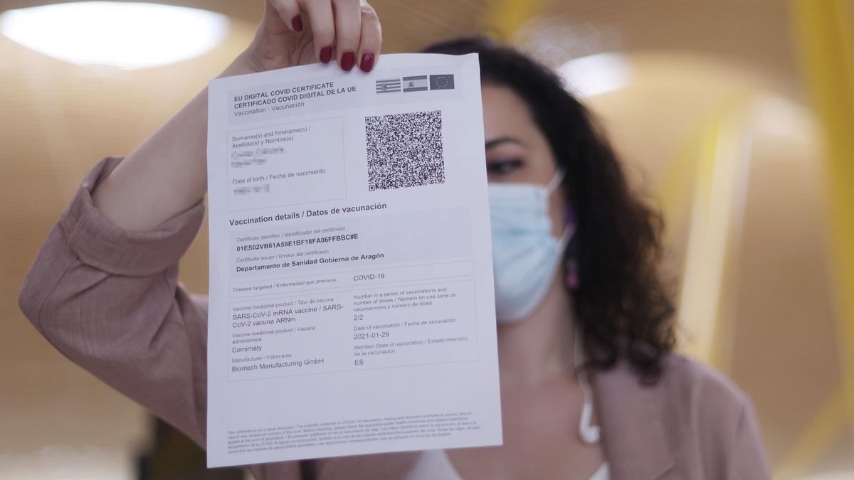 Una mujer muestra una copia en papel de su certificado Covid antes de coger un avión.