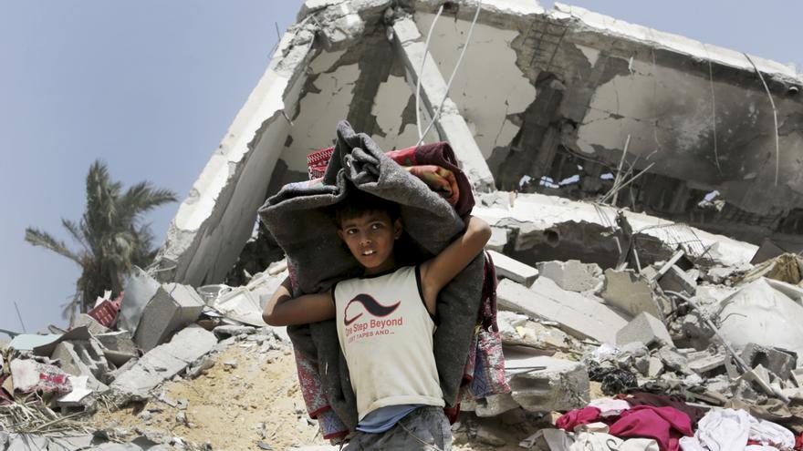 Un niño palestino rescata lo que puede de sus pertenencias de los escombros de su casa, destrozada por un ataque israelí en Juzaa, al este de Khan Younis, en el norte de la Franja de Gaza, agosto 2014 © AP Photo / Adel Hana