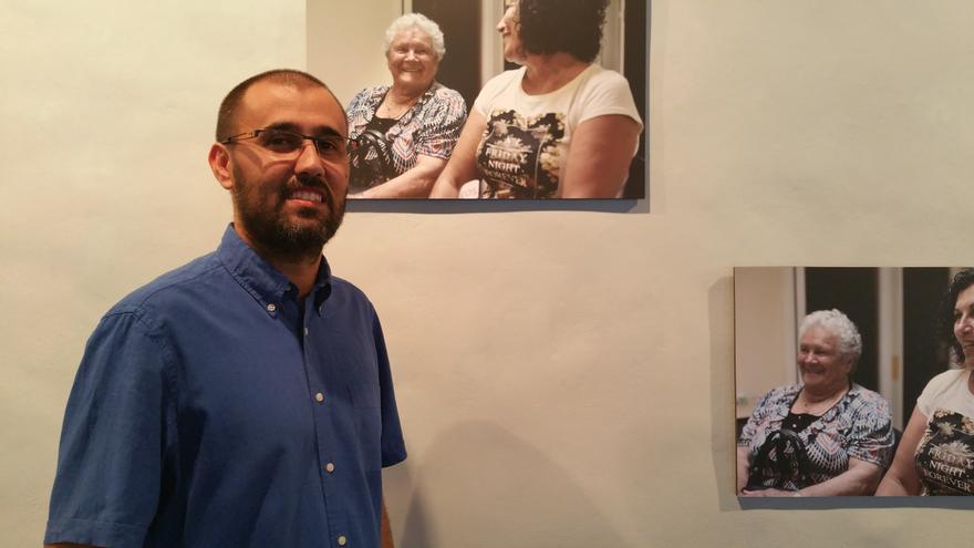 Azuquahe Pérez junto a fotografías de la exposición. Foto: LUZ RODRÍGUEZ.