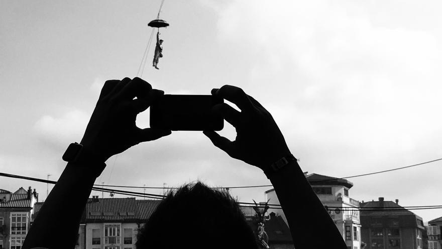 Asistentes al chupinazo fotografían el descenso de Celedón